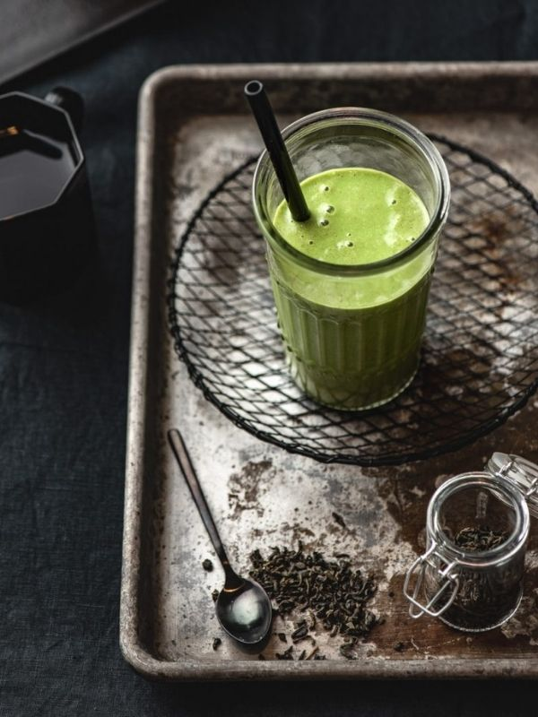 green tea smoothie in medium glass with black straw on metal tray