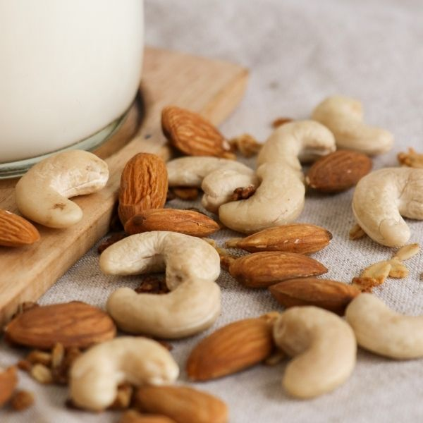 fresh almond and cashew nuts with glass of nut milk