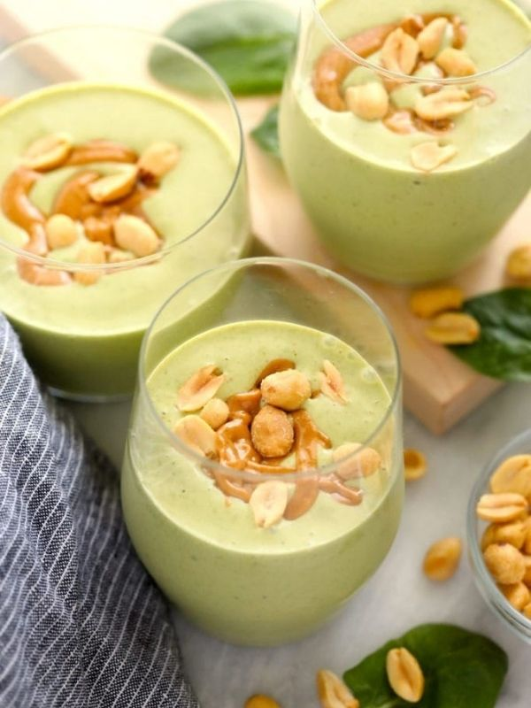 three peanut butter green smoothies in small glasses topped with peanuts