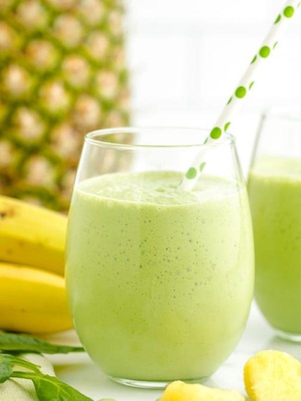pineapple spinach green smoothie in short glass with green spotted straw