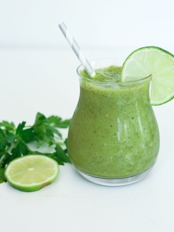 green smoothie in small glass with paper straw and lime wedge