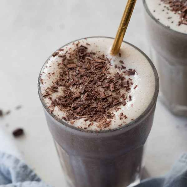 coffee lovers protein shake in glass with gold straw